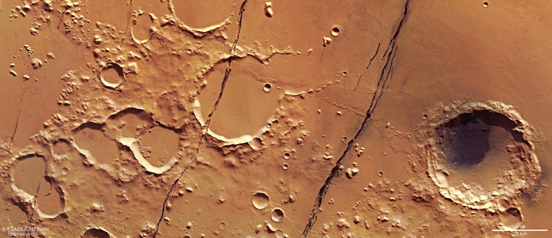 從歐洲太空總署(ESA)火星快車號(Mars Express)軌道衛星於2018年1月拍攝的這張影像中,可以看到布滿隕石坑的火星表面有好幾道深深的裂縫,這些裂縫是位於火星赤道附近科柏洛斯槽溝系統的一部分。IMAGE BY ESA