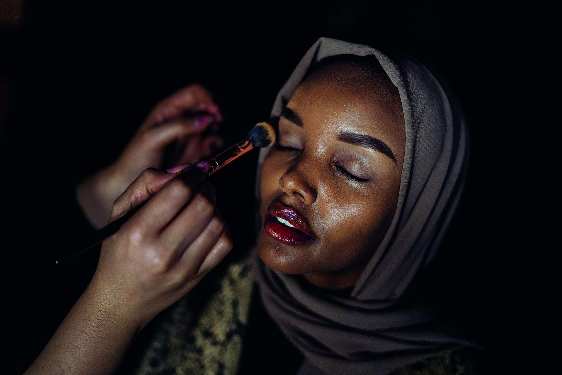 哈麗瑪.阿登戴著頭巾登上英國《時尚》雜誌以及《運動畫刊》2019年泳裝特刊的封面時,打破了許多成規。圖中,她正在土耳其伊斯坦堡的端莊時裝週由人幫她化妝,這個時裝週頌揚的是時尚的另外一面。阿登是出生於肯亞的索馬利難民,後來移民美國,是明尼蘇達州美國小姐選美比賽中第一位穿戴頭巾與布基尼的參賽佳麗。攝影:漢娜. 雷耶斯. 莫拉雷斯HANNAH REYES MORALES