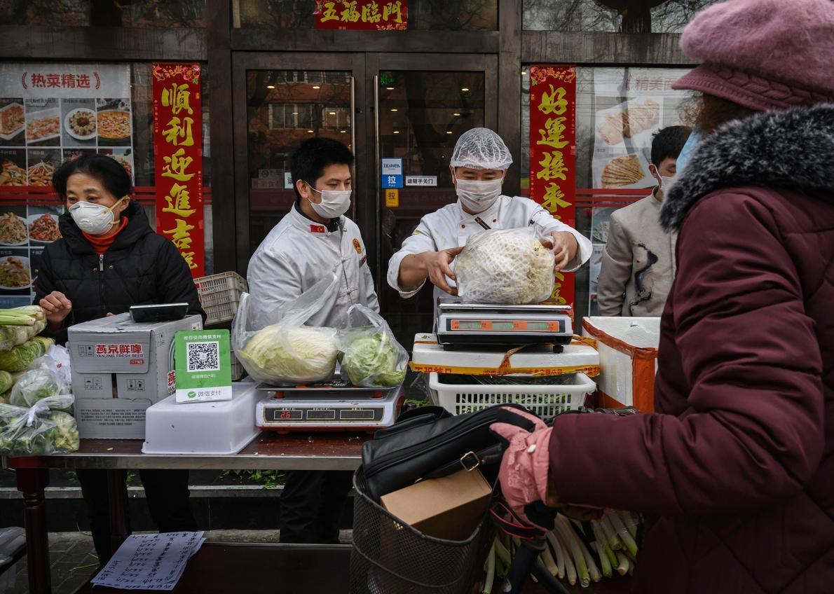 北京的攤販賣蔬菜時戴著防護口罩。一份2014年的研究發現,只有5%的北京居民曾在前一年內吃過野生動物。PHOTOGRAPH BY KEVIN FRAYER, GETTY