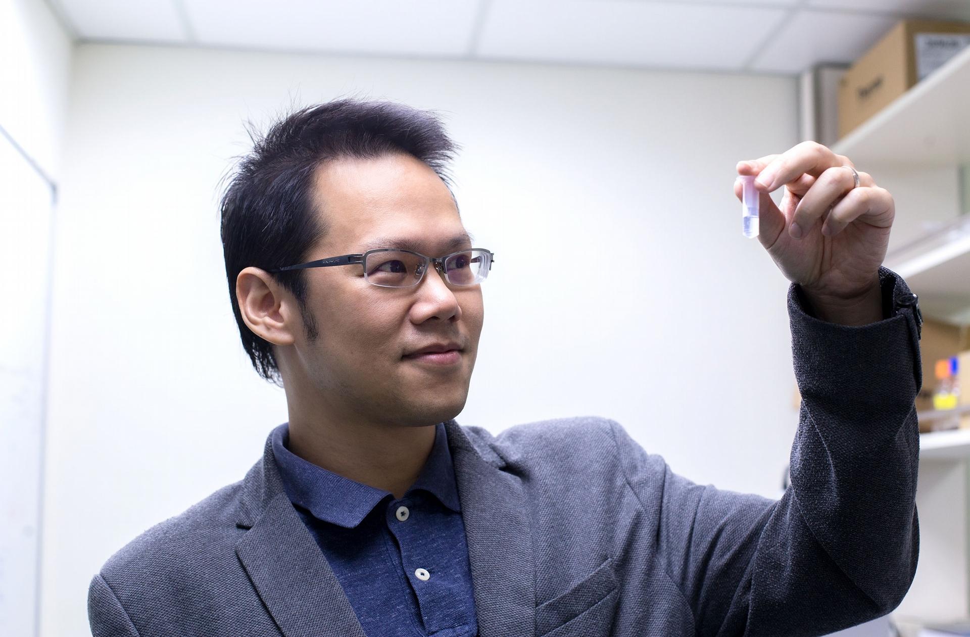 胡哲銘看著自己發明的冠狀病毒奈米疫苗,小小的容器裡充滿了 10,000,000,000,000 個薄殼中空奈米粒子。 攝影│林洵安