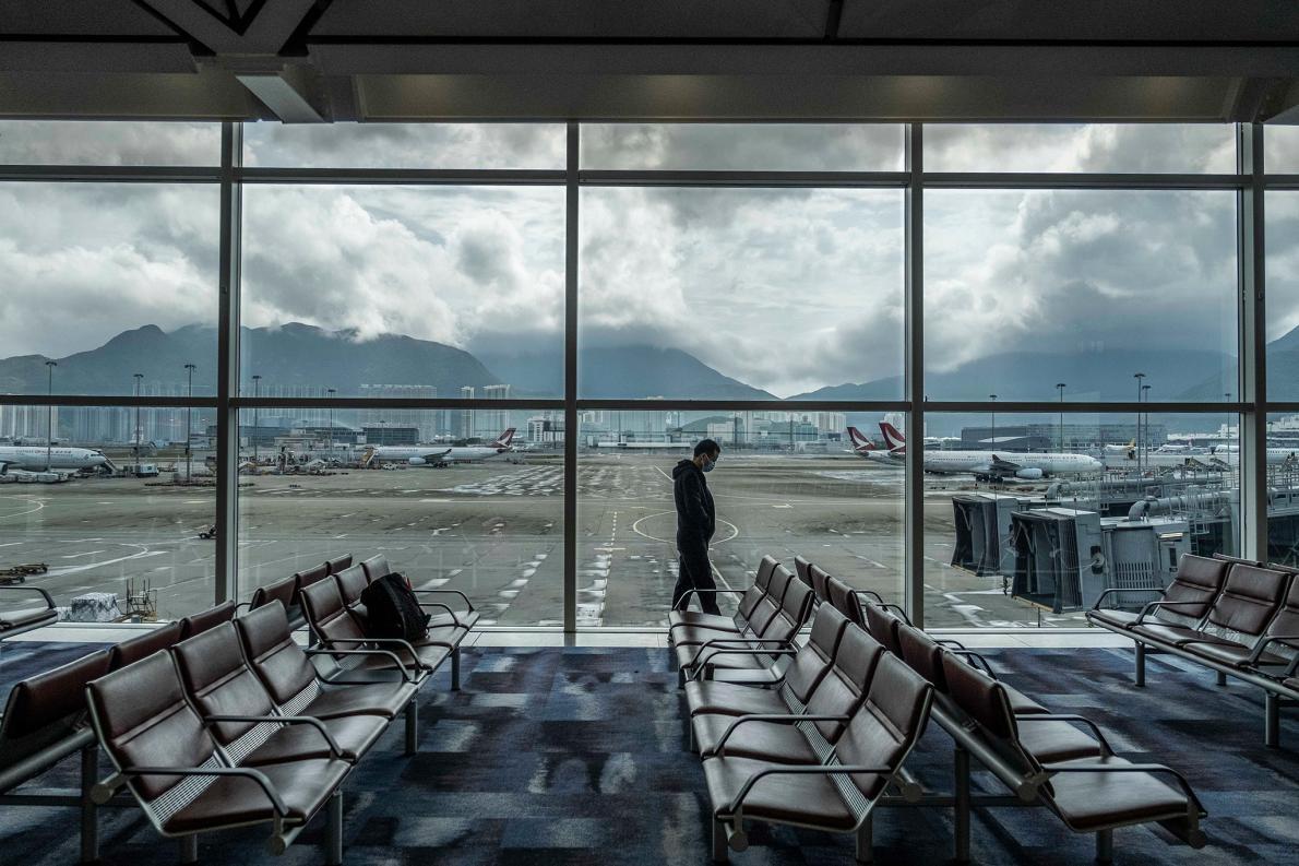 2月14日,一名男子走過香港國際機場的窗邊。 PHOTOGRAPH BY LAM YIK FEI, THE NEW YORK TIMES