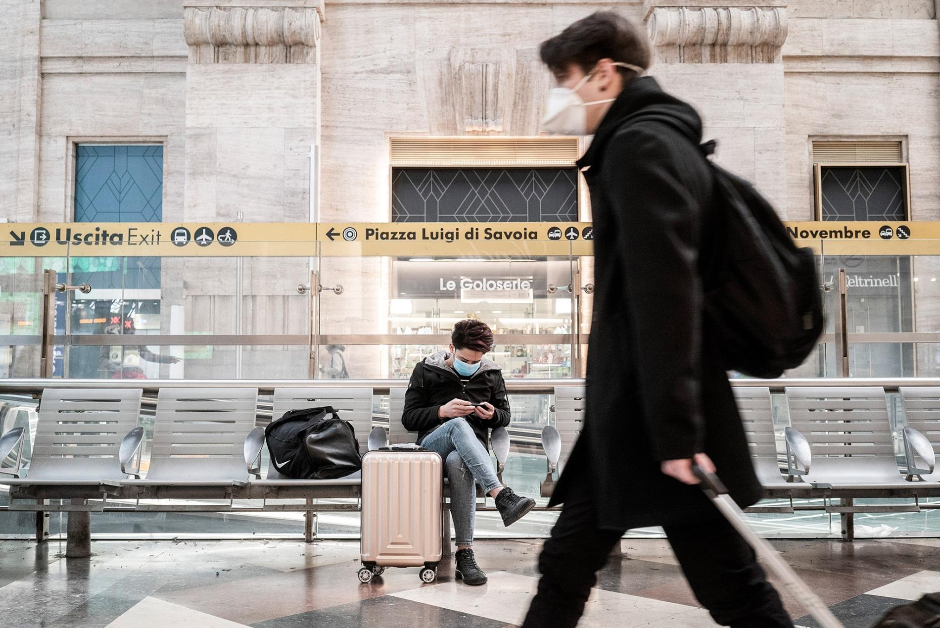 在義大利於3月8日的新版旅遊限制生效之前,一名旅客正在等候一班從米蘭中央車站出發的火車。PHOTOGRAPH BY ALESSANDRO GRASSANI, THE NEW YORK TIMES/REDUX