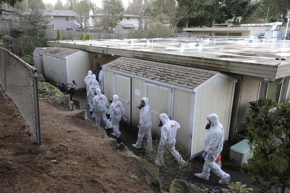 2020年3月11日星期三,Servpro災後重整公司的工作人員身穿防護裝和防毒面具,走進位於美國華盛頓州科克蘭(Kirkland)的生命照護中心(Life Care Center),準備開始清潔消毒。這間安養院位在西雅圖附近,正是華盛頓州爆發最多新型冠狀病毒疫情的地區。PHOTOGRAPH BY TED S. WARREN, AP IMAGES