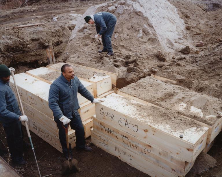 1992年2月,里克斯島矯正中心的受刑人正在埋葬棺材。PHOTOGRAPH BY JOEL STERNFELD