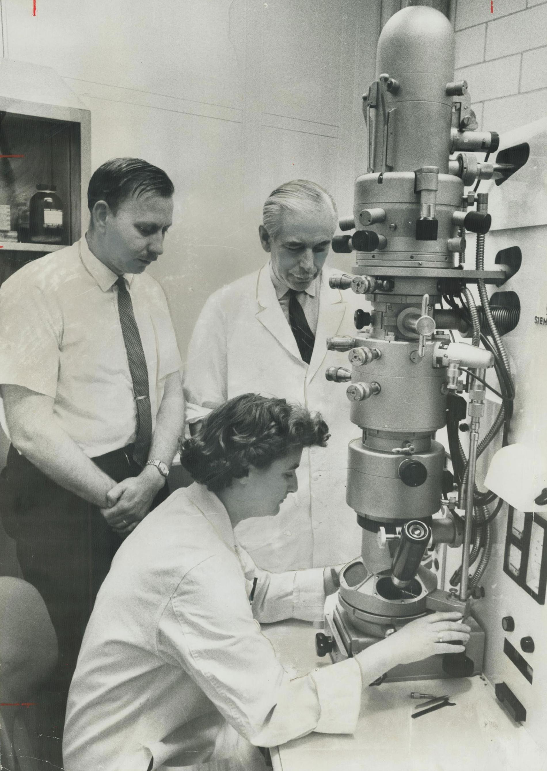 1963年,在加拿大多倫多的安大略癌症研究中心裡操作電子顯微鏡的科學家茱恩‧艾爾梅達。一年之後,艾爾梅達將成為第一個用她自己研發出來的顯微技術看到冠狀病毒的人。PHOTOGRAPH BY NORMAN JAMES, TORONTO STAR/GETTY
