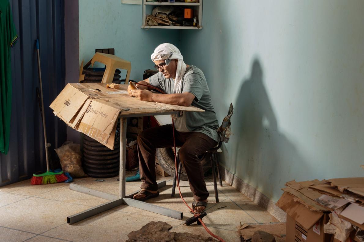 摩洛哥艾尼夫(Alnif)艾哈邁迪三葉蟲中心(Ihmadi Trilobites Center)的店主默罕.艾哈邁迪(Mohand Ihmadi)正在清理即將出售的棘龍牙齒。多年以來,艾哈邁迪會將他經手最珍稀的化石保存下來,期盼未來能成立博物館。「保存我們的過去很重要,」他說:「如果我們將過去丟失,就再也找不回來了。」PHOTOGRAPH BY PAOLO VERZONE, NATIONAL GEOGRAPHIC