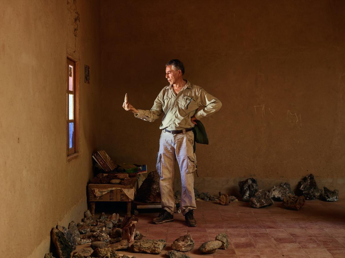 薩米爾.祖赫里於摩洛哥陶烏茲村民家中檢視一根巨大的棘龍牙齒。活動於這個地區的古生物學家會和當地人建立聯繫以確保具有科學價值的化石能被送進公共信託機構。 PHOTOGRAPH BY PAOLO VERZONE, NATIONAL GEOGRAPHIC