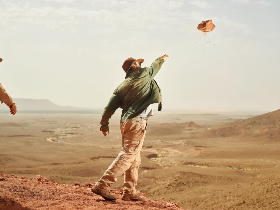 為了從棘龍發掘現場清掉多餘的岩塊,尼札.伊布拉希姆朝山下扔出一塊紅色砂岩。 PHOTOGRAPH BY PAOLO VERZONE, NATIONAL GEOGRAPHIC