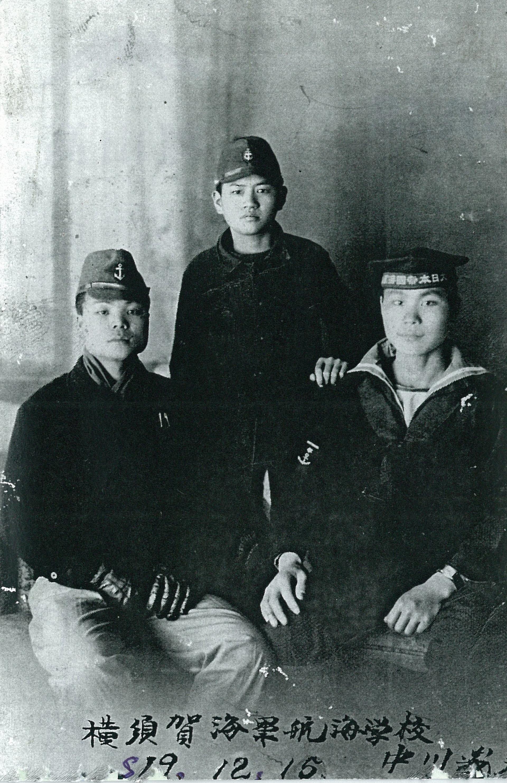 太叔公陳臣銅(右)與陳臣我(左)兄弟合影,1944年拍攝。 陳臣銅為第二期臺灣海軍特別志願兵,1944年11月在高雄左營受訓完畢後,因成績優異,被軍方派往橫須賀海軍航海學校培訓,然在赴日途中,所乘之船「護國丸」遭美軍潛艇擊沉,太叔公倖存下來。不過他的行李全沉入海,於是與早先赴日擔任海軍工員(少年工)的弟弟臣我相約見面,跟他借大衣穿,在東京留下此張合照(站立者兩兄弟的鄰居,亦為少年工)。 照片提供:陳柏棕