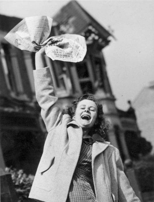 倫敦人在1945年5月8日歡慶德國投降──是德國在柏林的第二次、也是最後一次投降的前一天。派特.柏吉斯(Pat Burgess),左,揮舞著手上宣布同盟國勝利的報紙,希望丈夫很快就能從德國的戰事中返國。PHOTOGRAPH BY REG SPELLER, FOX PHOTOS/HULTON ARCHIVE/GETTY