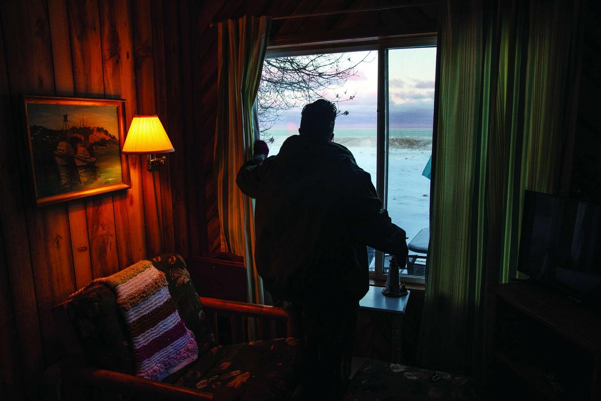 2020年2月8日休倫湖 在密西根州的奧斯科達,伊蓮娜.麥肯錫從她的一棟出租度假小屋審視著休倫湖。湖邊厚厚的冰層通常能保護湖岸不受風暴侵襲,但去年冬天很暖,湖浪侵蝕了岸邊的房產,造成數千美元的損失。Photo by AMY SACKA(艾米.薩卡)