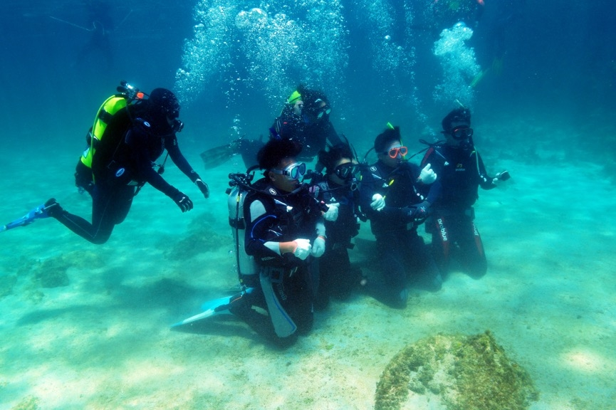 第一次潛水重裝下水總是令人興奮且緊張,因學員仍未習慣在海中的零重力,因此仍須與潛伴之間互相抓緊以穩定姿勢。攝影:朱雲瑋