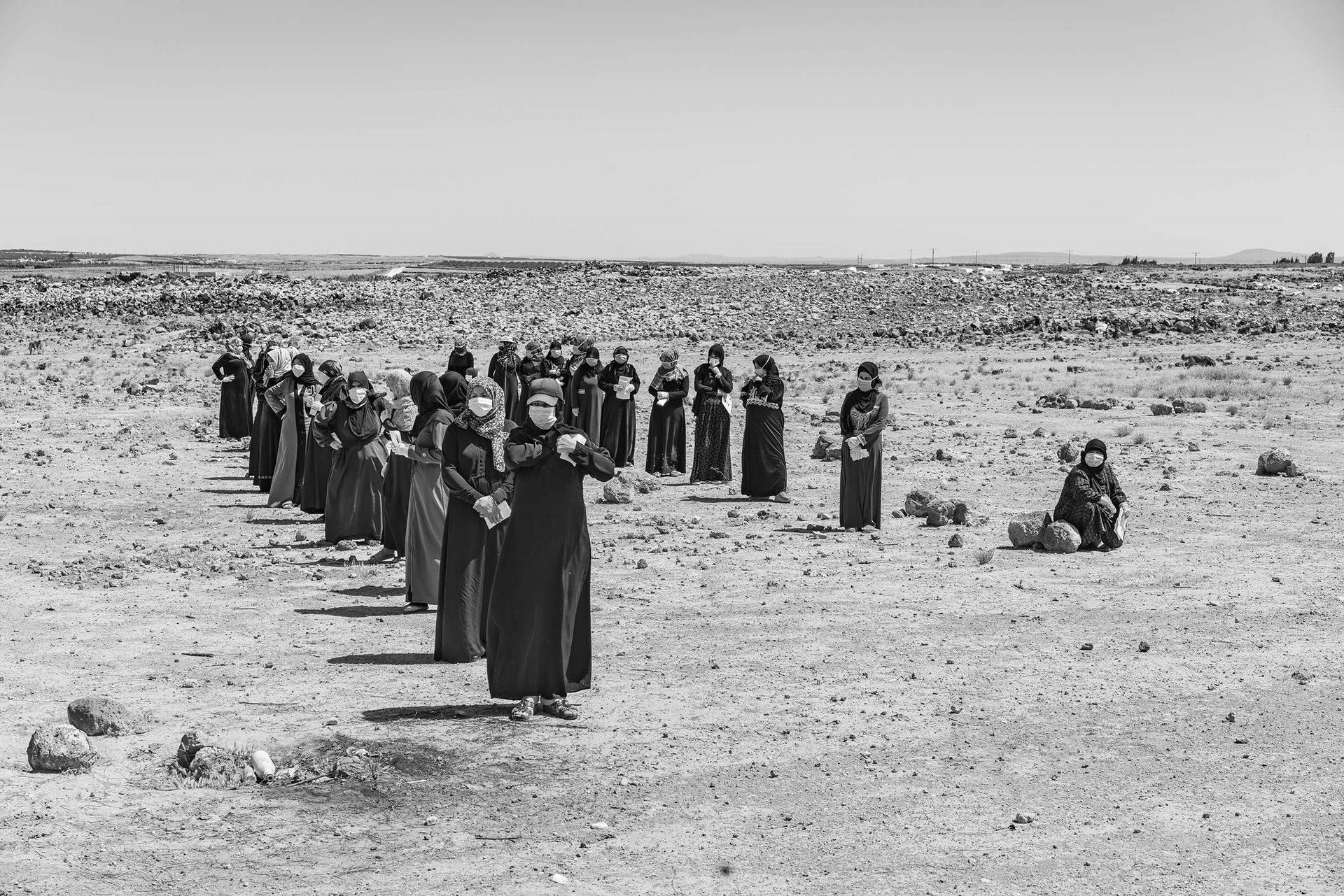 敘利亞難民婦女在沙漠中保持適當距離排隊,等待領取聯合國兒童基金會的捐贈物資,包括衛生用品和其他必需品。她們和家人住在麥夫拉格郊外的帳篷營地;數十萬其他難民住在特殊營地或是都市社區。在那些較為擁擠的區域,保持社交距離是遙不可及的奢侈。攝影:摩伊西斯.薩曼 MOISES SAMAN