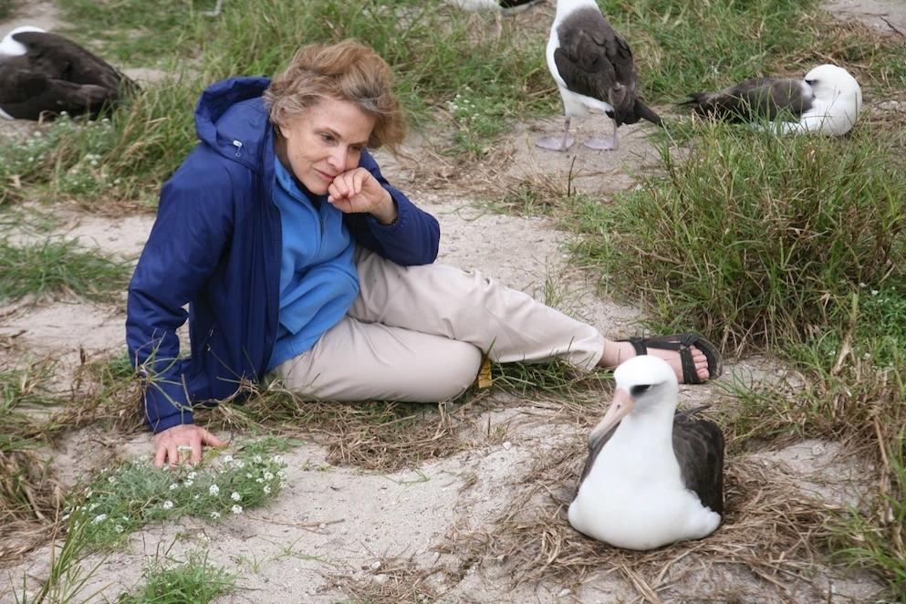 2012年1月,國家地理駐會探險家席薇亞.厄爾(Sylvia Earle)在砂島上坐在智慧旁邊。砂島是中途島動物保護區的一部份,而厄爾是海洋生態系的先驅研究者。PHOTOGRAPH BY SUSAN MIDDLETON