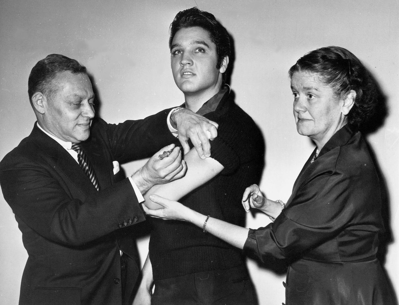 1956年,「貓王」艾維斯.普里斯萊(Elvis Presley)在參加艾德.蘇利文秀(The Ed Sullivan Show)錄影之前,在後臺接種脊髓灰質炎疫苗。 PHOTOGRAPH VIA ASSOCIATED PRESS
