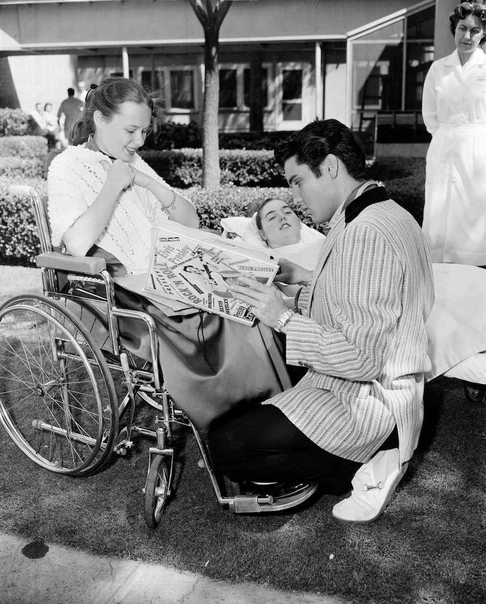1957年5月,貓王在加州探望脊髓灰質炎患者貝絲.克立爾(Beth Currier, 14歲),左,和依蓮.布洛克威(Elaine Brockway, 17歲)。坐輪椅的克立爾給貓王看她的剪貼簿,大多是她靠嘴巴做出來的。PHOTOGRAPH VIA ASSOCIATED PRESS