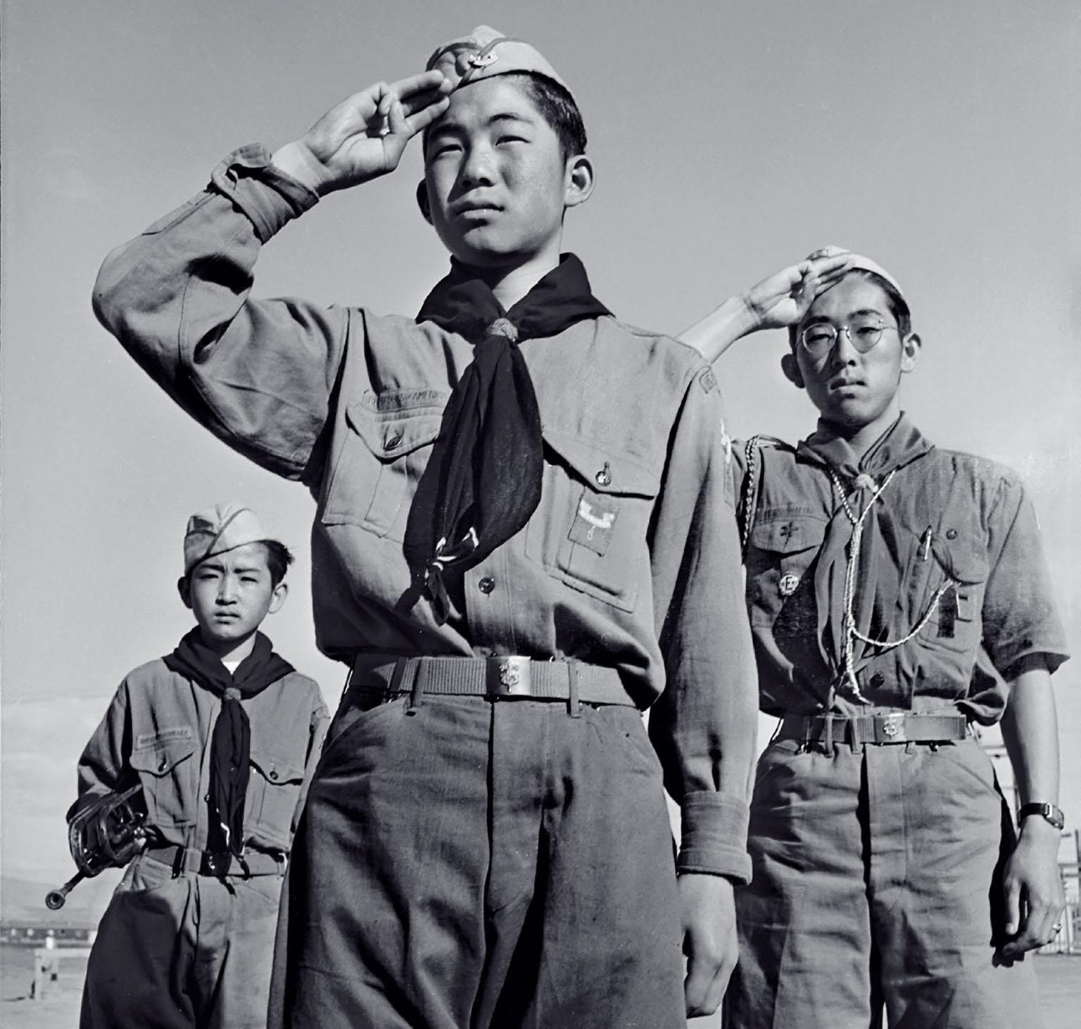 1943年,在懷俄明州的哈爾德山安置中心,三名童子軍,14歲的大原.傑克.準三、14歲的元安丈史和16歲的愛德華.加東哲二向美國國旗敬禮。當時他們被拘禁在加州聖塔阿尼塔集合中心和懷俄明州的哈爾德山安置中心。 PAT COFFEY, NATIONAL ARCHIVES