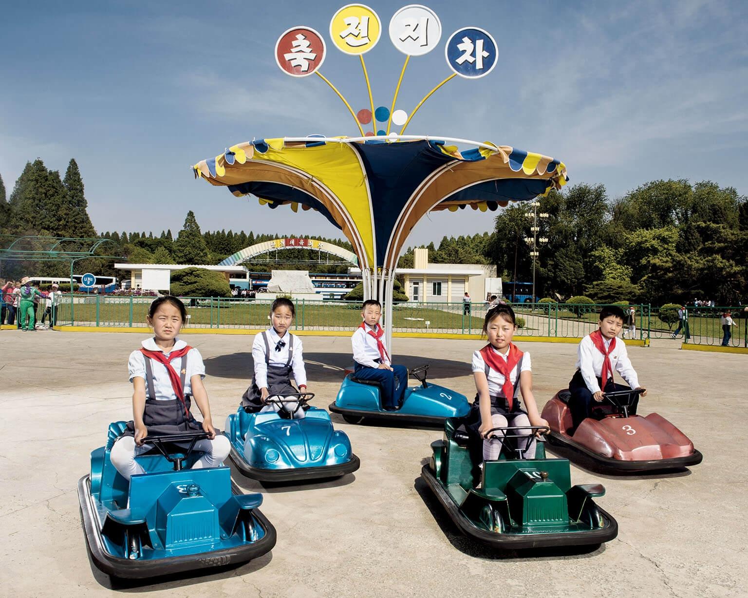 平壤郊區的「萬景臺遊樂園」內,玩碰碰車的兒童停下來拍照。在這個極權國家,居民鮮少有擺姿勢拍照的經驗。