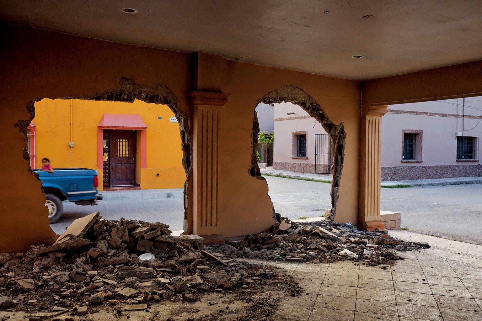 走過阿延第的警察局、消防局和軍事崗哨附近的街道,觸目可及都是塞塔斯集團拆毀的一些住宅與商店。大屠殺發生時,當時的市長還住在這棟房子的對街,他最初在報告中說沒有看到任何暴力行為的跡象。 攝影:柯爾斯登.魯斯 Kirsten Luce