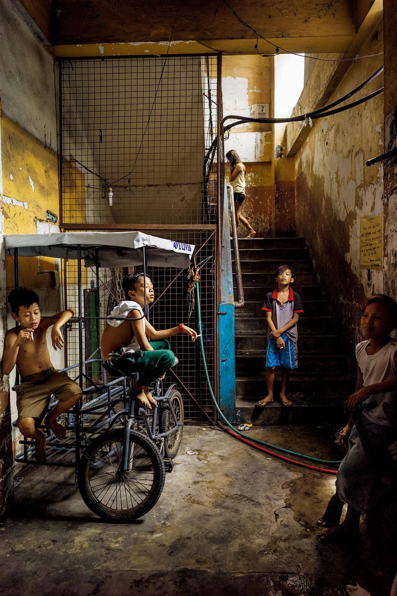 男孩坐在一輛由腳踏車改造的人力車上,悠哉地吞雲吐霧。菲律賓籍的歷史學家貝納蒂塔.丘吉爾說,在菲律賓很少見到那麼年輕的孩子抽菸。 攝影: 馬利午許. 雅尼謝夫斯基 Mariusz  Janiszewski