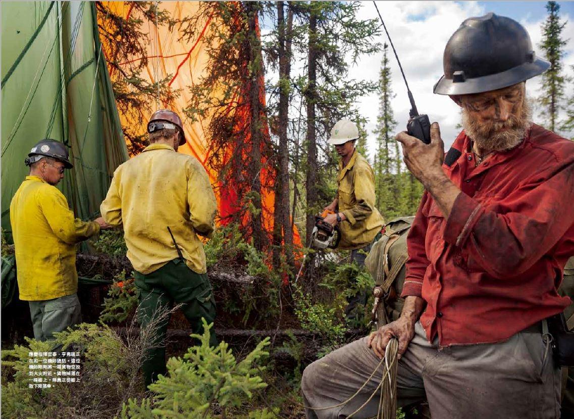 應變指揮官泰.亨弗瑞正在和一位機師通話。這位機師剛剛將一箱貨物空投到大火附近。貨物掉落在一棵樹上,隊員正從樹上取下降落傘。