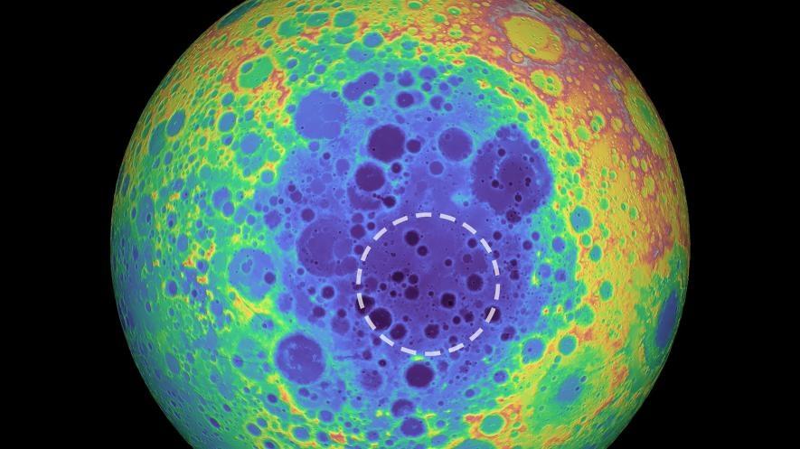 這張偽色影像是月球背面的地形圖,較暖的色調顯示海拔較高的區域,而較冷的色調則顯示海拔較低的區域。虛線圓圈表示南極-艾托肯盆地下方的質量異常區域。IMAGE BY NASA/GODDARD SPACE FLIGHT CENTER/UNIVERSITY OF ARIZONA