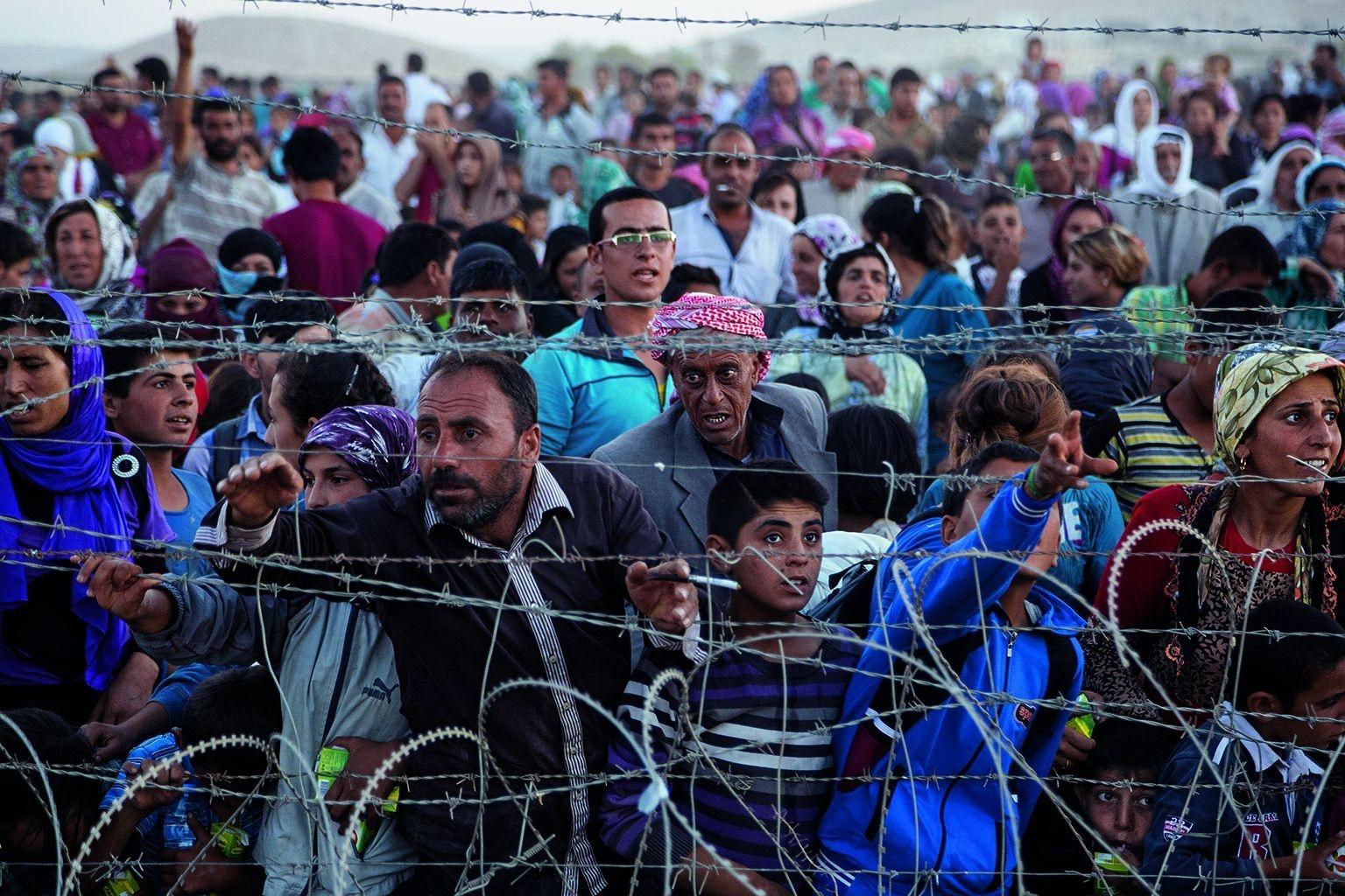 因為位於敘利亞艾因阿拉伯的家園遭到攻擊而出逃的庫德人,在土耳其邊境上的一片帶刺鐵絲網圍籬前推擠。攝影:約翰.史坦邁爾 John Stanmeyer