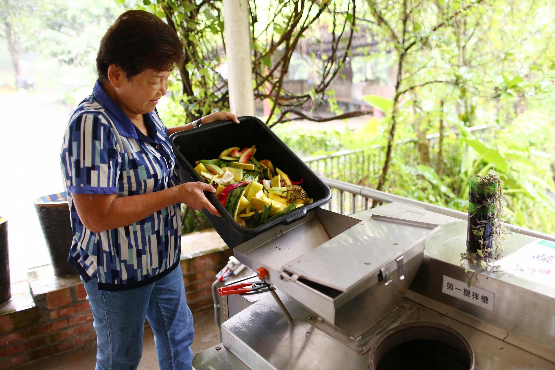 卓陳明將果皮殘渣倒入廚餘處理機中。由於遊客在享用農場內種植的蔬果作物食材後,同時也產生許多廚餘或剩食問題,部分廚餘可用於農場禽畜動物飼養之用,其他則是應用花蓮農改場研發的廚餘雙槽處理機將廚餘細碎化、瀝油瀝水、攪拌乾燥,每日可將1.5公斤廚餘製作成約0.5至1公斤無味的粉狀堆肥,將之與有機質肥料混拌後則再度施用於農場的土壤中,提供作物生長的養分,達到循環利用效益。(攝影:林韋言)